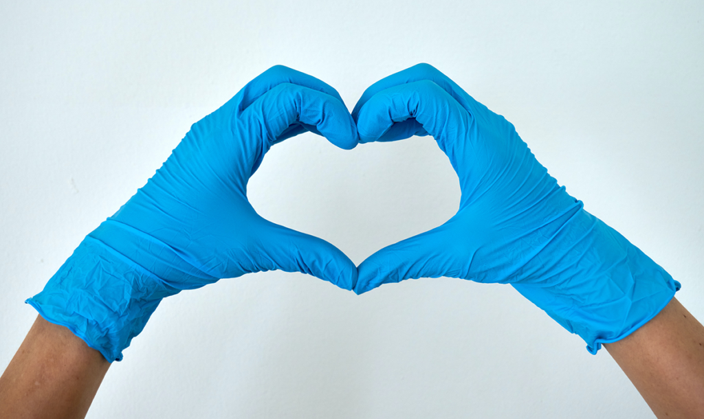Gloved hands making a heart shap